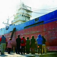 People on March 10 are dwarfed by the Kyotoku Maru No. 18, which was left stranded on a pier in Kesennuma, Miyagi Prefecture, by the March 11, 2011, tsunami. Officials said Monday the vessel will be dismantled in April. | KYODO