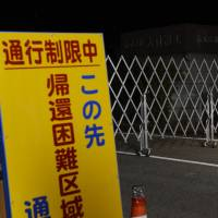 No entry: A road leading to an area in Tomioka, Fukushima Prefecture, where residents' prospects for returning home are up in the air, is blocked early Monday under its new evacuation zone designation. | KYODO