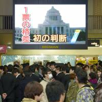 Surprise verdict: A monitor at Umeda Station in the city of Osaka carries the news of the unprecedented decision Monday by the Hiroshima High Court to nullify the results of the December Lower House election in the Hiroshima No. 1 and 2 districts. | KYODO