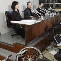 Recognized: Hiroshi Nakajima (center), who became paralyzed when the front wheel came off his Italian-brand bicycle in 2008, faces the media Monday after the Tokyo District Court sided with his damages claim against the bike's importer. | KYODO