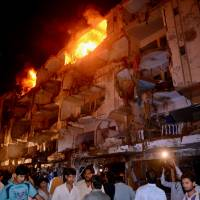 Explosive region: People gather at the site of bomb blast that left at least 37 dead in Karachi on Sunday. | AFP-JIJI