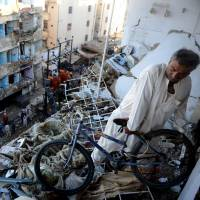 More carnage: A man moves a bicycle from his damaged home near the epicenter of a bomb blast in Karachi on Monday, following an attack a day earlier that killed at least 45 people. | AFP-JIJI