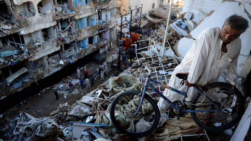 More carnage: A man moves a bicycle from his damaged home near the epicenter of a bomb blast in Karachi on Monday, following an attack a day earlier that killed at least 45 people.