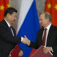 New history: Presidents Xi Jinping of China and Vladimir Putin of Russia exchange agreements in Moscow on Friday. | AP