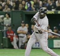 Boston's David Ortiz hits a solo homer off Hanshin's Yuya Ando in the first inning of their exhibition game at Tokyo Dome on Saturday. The Red Sox won 6-5. | AP PHOTO