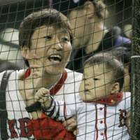 A Red Sox fan and a baby enjoy Major League Baseball's Opening Day action on Tuesday at Tokyo Dome. | AP PHOTO