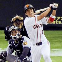 Yomiuri shortstop Hayato Sakamoto hits a grand slam in the fifth inning to help the Giants beat the Hanshin Tigers 9-1 on Sunday at Tokyo Dome. | KYODO PHOTO