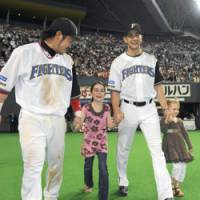Family values: Brian Sweeney smiles as he walks on the field with daughters Ava (left) and Mia, following his victory against the Chunichi Dragons on May 24 at Sapporo Dome. | KYODO PHOTO