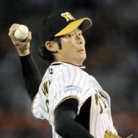 Start of showdown: Central League-leading Hanshin Tigers starter Minoru Iwata delivers a pitch against the second-place Yomiuri Giants at Koshien Stadium on Saturday. | KYODO PHOTO