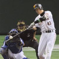 Nice rip: Kazunari Tsuruoka of the Yomiuri Giants cracks a solo homer in the third inning of Game 3 of the second stage of the Central League Climax Series against the Chunichi Dragons at Tokyo Dome on Friday night. The game finished in a 5-5 tie after 12 innings. | KYODO PHOTO
