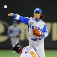 Quick toss: Seibu second baseman Hiroshi Hirao throws the ball to first after making a forceout at second to complete a double play in the first inning against the SK Wyverns in the Asia Series at Tokyo Dome on Thursday. The South Korean club edged Seibu 4-3. | KYODO PHOTOS