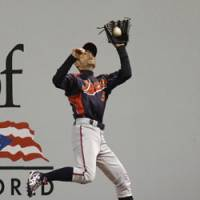 Hauling it in: Right fielder Ichiro Suzuki makes a running catch on a flyball hit by South Korea's Jeong Keun Woo in the fifth inning on Thursday night. | AP PHOTO