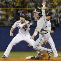 Missed opportunity: Hanshin Tigers baserunner Takahiro Arai is tagged out by Hiroyasu Tanaka in an attempt to steal second during the third inning on Wednesday at Jingu Stadium. The Swallows won 4-2. | KYODO PHOTO