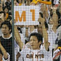 Simple mathematics: A Giants supporter holds up a sign that indicates the team only needs a victory or a tie on Wednesday to clinch its third consecutive Central League title. | KYODO PHOTO