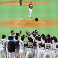 Party time: The Fighters gather at home plate to celebrate Terrmel Sledge's game-winning grand slam in the bottom of the ninth inning against the Eagles at Sapporo Dome on Wednesday. | KYODO PHOTO
