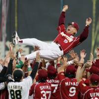 Unified act: Members of the Fighters and Eagles toss Rakuten skipper Katsuya Nomura in the air after his final game as the team's dugout boss. | KYODO PHOTO