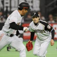 A miscue: Fighters starter Masaru Takeda fails to pick up a bunt by Takuya Kimura of the Giants during the fifth inning of Game 1 of the Japan Series on Saturday. | KYODO PHOTO