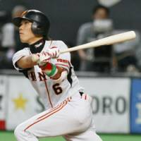 Heroic performance: Yomiuri Giants shortstop Hayato Sakamoto hits a two-run double in the fifth inning of the opener of the Japan Series against the Hokkaido Nippon Ham Fighters on Saturday at Sapporo Dome. The Giants won 4-3. | KYODO PHOTO