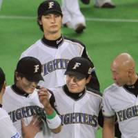 Live to fight another day: Fighters captain Atsunori Inaba (bottom left) is consoled by teammates following the Fighters' loss in Game 6 of the Japan Series on Sunday. | KYODO PHOTO