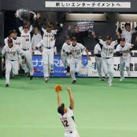 Frozen in time: Marc Kroon celebrates the final out of the Japan Series as his Yomiuri Giants teammates spill out onto the field on Saturday night at Sapporo Dome. | KYODO PHOTO