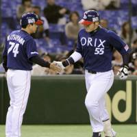 Celebrating touch: Orix's Takahiro Okada is congratulated by coach Hideaki Matsuyama after hitting a third-inning solo home run against Nippon Ham on Tuesday at Tokyo Dome. Orix won 8-4. | KYODO PHOTO