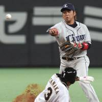 Steady defense: Lions shortstop Hiroyuki Nakajima throws the ball to first after forcing out the Fighters' Kensuke Tanaka in the third inning at Sapporo Dome on Friday. Saitama Seibu beat Hokkaido Nippon Ham 6-4. | KYODO PHOTO