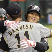 Slam bam: Fighters pitcher Yu Darvish embraces Atsunori Inaba after the slugger's grand slam on Saturday. | KYODO PHOTO