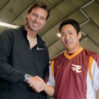 Special visit: Former MLB great Randy Johnson shakes hands with Tohoku Rakuten's Masahiro Tanaka at Tokyo Dome on Tuesday night. | KYODO PHOTO