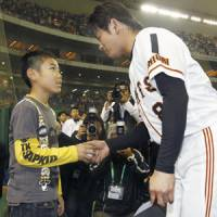 Touching gesture: The Giants' Yoshitomo Tani hands his grand-slam home run ball to 10-year-old Koki Kimura, the son of former Yomiuri coach Takuya Kimura, who died on April 7, after Saturday's game at Tokyo Dome. Tani's dramatic eight-inning homer propelled the Giants to a 7-4 victory. | KYODO PHOTOS