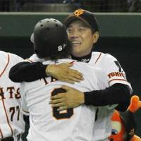 Warm embrace: Giants manager Tatsunori Hara hugs Yoshitomo Tani after his pinch-hit grand slam in the eighth inning on Saturday.