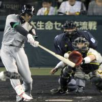 Sweet spot: The Fighters' Atsunori Inaba hits an opposite field, two-run homer in the top of the ninth inning to lead Hokkaido Nippon Ham to a 4-2 victory over the Hanshin Tigers at Koshien on Wednesday. | KYODO PHOTO