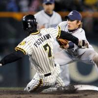 Not fast enough: Hanshin baserunner Shunsuke Fujikawa is tagged out by Seibu infielder Yasuyuki Kataoka as he attempts to steal second in the fifth inning on Wednesday at Koshien Stadium. The Lions won 3-1. | KYODO PHOTO