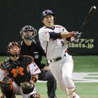Over the fence: Yakult Swallows outfielder Yasushi Iihara hits a solo home run off Yomiuri starter Shun Tono in the seventh inning on Tuesday night at Tokyo Dome. | KYODO PHOTO