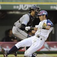 Home sweet home: Orix's Makoto Moriyama slides home safely on an RBI single by Takahiro Okada during their game against the Fighters on Wednesday at Skymark Stadium in Kobe. Orix won 5-1. | KYODO PHOTO