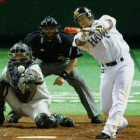 Back to front: Softbank's Jose Ortiz hits a two-run single against the Lions on Monday. | KYODO PHOTO