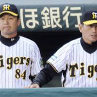 Disappointing result: Tigers coach Yasuo Kubo (left) and manager Akinobu Mayumi watch the Giants score five runs in the seventh and eight innings to rally past Hanshin and end the hosts' title aspirations on Sunday at Koshien Stadium. | KYODO PHOTO