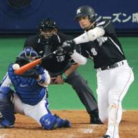 Getting the job done: Chiba Lotte's Toshiaki Imae lashes a run-scoring hit in the third inning against Chunichi in Game 1 of the Japan Series on Saturday at Nagoya Dome. The Marines beat the Dragons 5-2. | KYODO PHOTO
