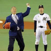 Living legend: Masaichi Kaneda, a 400-game winner during his illustrious pitching career, tosses the ceremonial first pitch and salutes the crowd before Game 3 of the Japan Series at Chiba Marine Stadium on Tuesday. | KYODO PHOTO