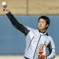 All eyes on me: Fighters rookie pitcher Yuki Saito plays catch during his first day of camp in Kamagaya, Chiba Prefecture, on Wednesday. | KYODO PHOTO