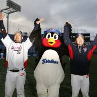 Saluting the fans: Infielder Kazuhiro Hatakeyama (left) and pitcher Masanori Ishikawa helped the Swallows earn a 4-2 win against the Dragons on Tuesday. | KYODO