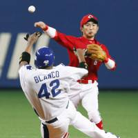 Straight and true: Hiroshima's Eishin Soyogi throws the ball to first base as Chunichi's Tony Blanco tries to slide into second during the Dragons' 5-4 win on Sunday. | KYODO