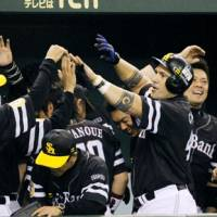 Night star: The Hawks' Alex Cabrera (right) is mobbed by teammates after hitting a two-run, eighth-inning double against the Giants on Thursday. Softbank defeated Yomiuri 2-1. | KYODO PHOTO