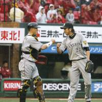 Tiger style: Hanshin's Kenji Johjima (left) and Kyuji Fujikawa celebrate the Tigers' 2-1 win over the Eagles on Sunday. | KYODO