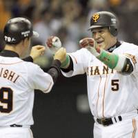 Getting the job done: Giants coach Takayuki Onishi congratulates slugger Alex Ramirez (right) after his solo home run in the sixth inning on Friday at Tokyo Dome. Yomiuri defeated the Tohoku Rakuten Golden Eagles 4-2. | KYODO PHOTO