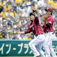 Communication breakdown: Daisuke Kusano (left) and Kazuo Matsui collide while chasing a fly ball during Tohoku Rakuten's 7-0 defeat to the Tigers on Sunday. | KYODO