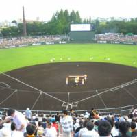 View from above: Kaiseizan Stadium in Koriyama, Fukushima  Prefecture, with its video screen-scoreboard, rough  dirt infield and smoke rising from a concession stand barbecue behind  the bleachers, just to the right of the backscreen. | WAYNE GRACZYK PHOTO
