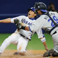 Touch of death: BayStars catcher Shinji Niinuma tags out Chunichi's Masahiko Morino on Sunday night. | KYODO