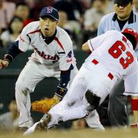 Thieves never prosper: Hiroshima's Yoshihiro Maru (63) tries in vain to steal third base against the Swallows on Thursday. | KYODO PHOTO