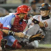 Coming through: Yomiuri's Yoshiyuki Kamei slides into Carp catcher Yoshiyuki Ishihara during the fourth inning on Sunday. Kamei was ruled out on the play. | KYODO
