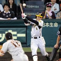 Stick control: The Tigers' Takashi Toritani strokes a game-tying single in the ninth inning against the Giants at Koshien Stadium on Friday. Toritani had three hits in the 4-4 tie. | KYODO